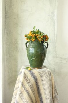 Green vase with yellow flowers
