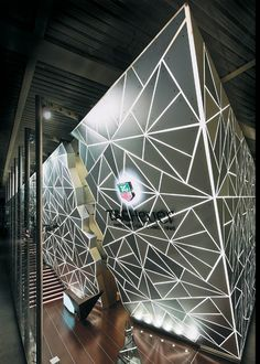 E.T. Exterior   Cut by lasers and designed with software used for automobile engineering, 560 aluminum triangles were laid over a membrane of a PVC-based material called Barisol to form the exhibit's exterior. Backlit by almost 1,000 fluorescent lights, the booth looked like a glossy onyx tower polished by inhuman hands.