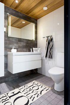 kylpyhuoneeseen valkokiilto allaskaappi sekä iso peili. tummaa lattiakaakelia, iso valkoinen seinäkaakeli. suihkujen kohdilla pienempi koristelaatta.