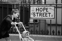 old photo of boy pushing a pushchair past a 'Hope Street' street sign