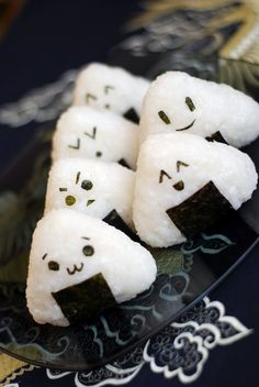 Onigiri is a rice ball wrapped with nori and filled with pickled fruits  vegetables or meat that made rice more convenient to pack in a lunch box and take out. It isn't always a ball though and comes in various shapes.
