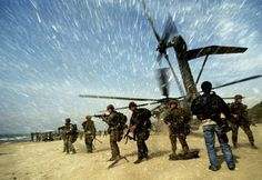 an-albanian-man-carries-a-child-to-a-us-marine-ch53-super-stallion-helicopter-as-it-lands-at-golame-beach-near-the-port-of-durres-in-this-march-16-1997-picture