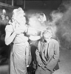 THE LIBERATION OF BERGEN-BELSEN CONCENTRATION CAMP, MAY 1945. After dressing in clean clothes, a woman inmate is dusted with DDT powder to kill the lice which spread typhus. The dusting is done by other former camp inmates (many of whom were trained nurses before being interned) under the supervision of the Royal Army Medical Corps.