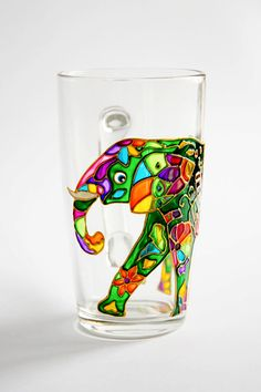This custom coffee mug features bright Indian elephant. Colorful flowers and pieces of abstract design is hand painted on the green background. It is
