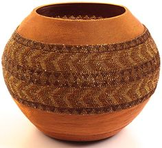 These pot shaped baskets are created only by masterweavers. First they make a traditional piece of pottery and then begin weaving over it. Each glass bead is individually threaded onto the copper wire and woven into the basket with very fine weaving. When the basket is complete, the pottery is intentionally cracked and removed from the inside.