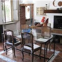 luminoso soggiorno con camino in cascina recuperata. Bei pavimenti in cotto con bordura in ceramica. Caratteristiche volte a botte con mattone a vista.
