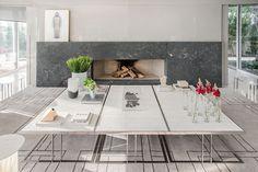 Decoração de casa ampla e confortável com ambientes integrados e pronta para receber, na sala uma lareira e mesa de centro branca com flores e plantas para decorar.