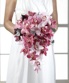 "Perfectly opulent with the use of pink and pale pink cymbidium orchids, accented with burgundy mini cymbidium orchids, Dusty Miller Stems, and lush greens, this cascade shaped bouquet gives new meaning to a blushing bride. A wonderful way to bring your bridal style to life! Approx. 18""H x 13""W."