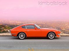 1972 Datsun 240Z Orange Profile View On Road Overlooking City Lights