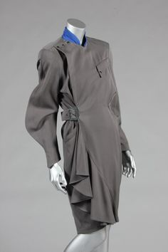 * Thierry Mugler `Les Milteuses' Communist-style dress, Autumn-Winter, 1986-7, labelled and size 38, of grey gabardine with royal blue stand collar, angular pockets, exaggerated shoulders, buckled belt to waist side.