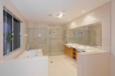 Perfect bathroom for two features light hardwood dual vanity cabinetry across from a large jacuzzi tub, with glass panels enclosing both shower and water closet functions.