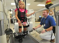 At the Riley Hospital for Children in Indianapolis on September 1, 2010, physical therapist Ryan Cardinal watches six-year-old Anna Good walk in a Hocoma Lokomat lower-extremity robot. The hospital's Robotic Rehabilitation Center is using robots to help youngsters with cerebral palsy and other movement disorders improve the use of their arms and legs. (AP Photo/The Indianapolis Star, Joe Vitti)