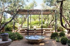 The outdoor dining space at Patrick Dempsey's Malibu home, is shaded by a metal-framed wicker canopy.