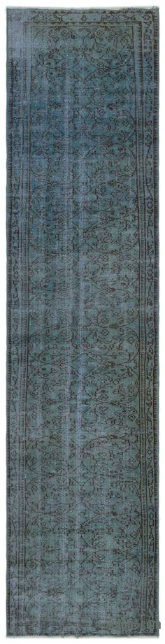 """For a contemporary look with abstract appeal, this blue over-dyed rug is skillfully crafted by the revitalization of a hand knotted vintage Turkish rug. Made from wool on cotton, this """"distressed"""" rug measures 2'8'' x 10'10'' (32 in. x 130 in.). The process in creating these works of art begins by shearing to lower the pile and to help """"distress"""" them. They then undergo a series of processes to remove the color. They are now ready to be dyed in one color, a stage that can be repeated severa…"""