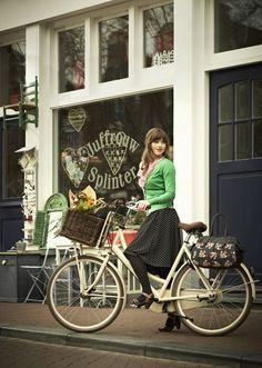 Women in tights... Women on bikes... — Cycle chic in green cardigan, black dotted skirt,...