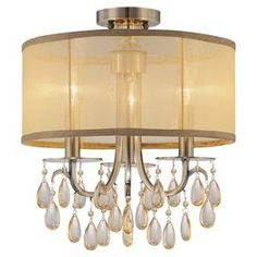 "Brass chandelier with a transparent drum shade and hanging crystal accents.   Product: ChandelierConstruction Material: Brass, silk, and crystalColor: Antique brass and gold shimmerFeatures: UL and cUL listedAccommodates: (3) 60 Watt candelabra base bulbs - not includedDimensions: 15"" H x 14"" Diameter"