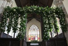 White flowers and green foliage on church altar screen