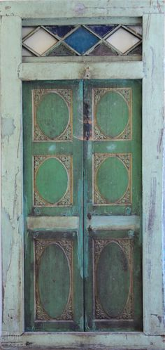 unique design of teal and green panels in wood door with white and blue glass in transom
