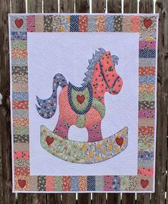 "Sweet appliqued rocking horse quilt made by Katie Wiseman from Katie's Quilts and Crafts for a friend's new baby.  ""Here I am quilting a wide whimisical feather stitch with variegated polyester longarm thread by Aurifil.""  To see more please visit http://katiesquiltsandcrafts.blogspot.com/2014/04/rocking-horse-baby-quilt.html"
