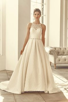 A stunning ball-gown dress with lace over satin and a key hole back.    <strong>Size: </strong>8 – 30 <strong>Colour: </strong>Ivory / Buttercup <strong>Fabric:</strong> Lace over Satin <strong>Style:</strong>Ball Gown <strong>Neckline:</strong>High Neck <strong>Laced or Zipped: </strong>Zipped