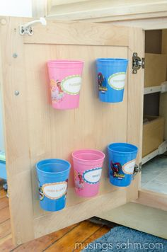 Here's the solution for organizing toothbrushes & toothpaste - attach cups to the back of the cabinet door with velcro. Easy & cheap! Read all about it here...