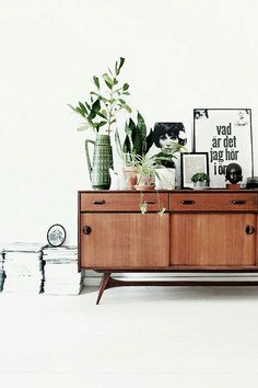 Consider a sideboard that doubles as a bar and storage. Gorgeous sideboard styling - love the plants and prints.