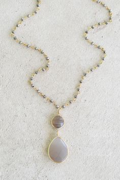 Dainty and classic beaded necklace with grey and gold accents. Teardrop and circle stone pendant hangs from a delicate beaded chain that adds the right amount of sparkle.