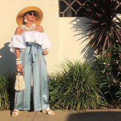 Off the shoulder top worn with high waist wide leg pants, sandals and statement accessories | Photo by Tamera Beardsley (@tamerabeardsley) | For more style inspiration visit 40plusstyle.com