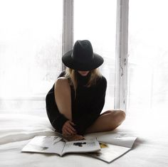 Dark clothes against light skin and surroundings. Hat, pose, props (light surroundings, bed/magazines)