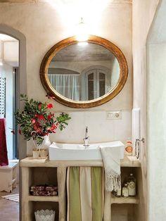 Piezas recuperadas como el espejo, muebles de obra que nos trasladan a otra época... una atmósfera ideal para un cuarto de baño muy particular.