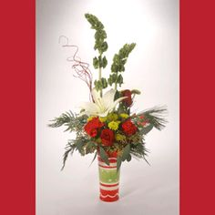 CHRISTMAS JUST BECAUSE: Simple yet lovely, this arrangement communicates a holiday sentiment through Lilies, Carnations, Roses, Bells of Ireland and seasonal evergreens in a holiday vase, which comes in 3 assorted designs.   #MatlackFlorist