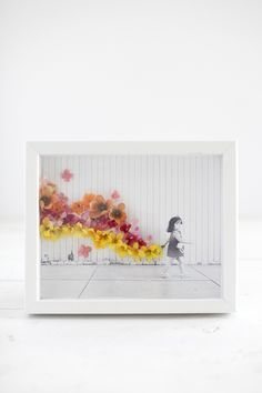 Turn a simple photo into a work of art with artificial flowers and hot glue.
