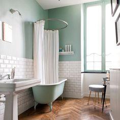Salle de bain dans les tons mint / vert d'eau ; parquet pointe de Hongrie ; baignoire sur pieds ; carreaux de métro