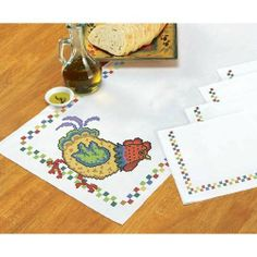 """Fiesta Table Runner & Napkins Stamped Cross-Stitch Kit by Herrschners. $14.99. Herrschners Exclusive! 5-Piece Set. This cute set is just what you need to turn your table into a party! Stamped for cross-stitch on white easy-care polyester/cotton fabric with a perle edge. Includes easy-to-follow instructions. Approximately 14 44"""" (36 x 112cm) table runner with four approximately 16 16"""" (41 x 41cm) napkins. Made in U.S.A."""