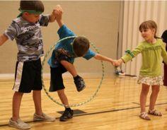 Corps + cerceaux + coopération - faire faire le tour de la ronde au cerceau sans se lêcher les mains - hoop relay