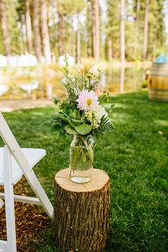 large mason jar on tree stump for aisle decor. See more of this vintage vineyard wedding. http://www.weddingchicks.com/2013/09/30/vintage-vineyard-wedding/