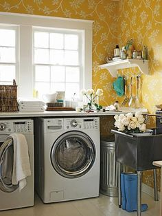Love this sunny yellow laundry room with white washer & dryer, bright yellow Farrow & Ball The Ringwold Papers Wallpaper and stainless steel industrial laundry sink.