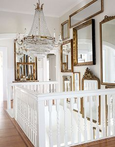 gallery wall of antique mirrors + chandelier