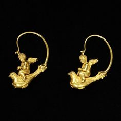 Earrings with a winged putto riding a dove . Italy, about 1870. Gold with granulation and filigree Date: ca. 1870 (made) Museum no.: M.7 Materials & techniques: Gold with granulation and filigree work Location: Jewellery, room 91, case 20, shelf D, box 5 Place: Italy