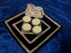 Handmade pooja thali made from maroon velvet adorned with rhinestone silver lace