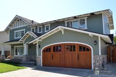 If you're going to have the garage out front, you better make it look nice, like this one.  Arched outswing carriage garage doors.