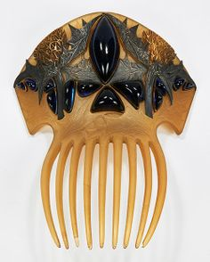Lalique's Sea Holly Comb.Rene Lalique's engineering genius is in full force here, because the silvery blue color on the leaves is achieved through the reflected light from the sapphire-colored glass cabochons. Sold at auction on 6 June 2015 for $205,000. from http://barbaraanneshaircombblog.com/