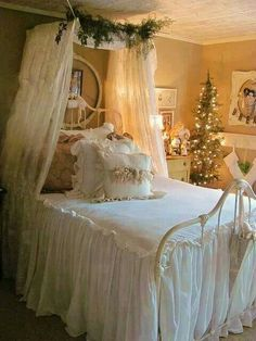 Canopy bed cover over a gorgeous bed, of lace, matching pillows trimmed with gold bows, and white lights. Note...Christmas tree next to bed.