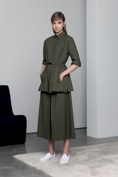 Spring 2015 Ready-to-Wear - Piazza Sempione -- Oversized, belted, half-sleeve shirt over front-pleated midi skirt in olive worn with white slip-ons.