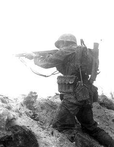 A Marine fires his Thompson submachine gun at enemy positions on Peleliu, September 1944.