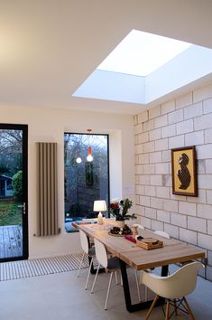 Light flooded dining area with oriel window seat and exposed blockwork wall in a rear extension to a Victorian property