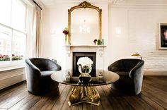 Gorgeous, gorgeous. High white walls, comfy armchairs, mirror and mantlepiece. Love all of the reflection and the clean white.