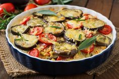Summer Veggie Gratin 1 large eggplant, cut into 1/2 inch thick slices 3 large tomatoes, cut into 1/2 inch thick slices 2-3 garlic cloves, roughly chopped 1/2 cup parmesan cheese, grated 1/2 cup swiss or gruyere cheese, grated 1 cup olive oil 1 teaspoon salt 1/2 teaspoon pepper Optional, fresh sage and rosemary for garnish