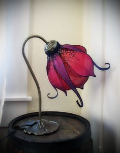 Bring a bit of magic to your home and gently light the night with this hand made one of a kind silk flower lamp. The flower is hand dyed and painted and mounted on an up-cycled, vintage, art nouveau style lily pad base. An orange hued energy efficient led bulb creates a soft glow. This lamp plug...