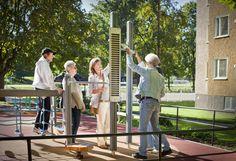 Activiteiten voor ouderen: Senioren en medewerkers van zorginstelling maken plezier in een beweegtuin. De oefeningen refereren naar het dagelijks leven.